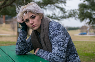 Woman sitting at table in park thinking about whether a food addiction hotline will help or not